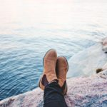 man's crossed ankles on shoreline rock